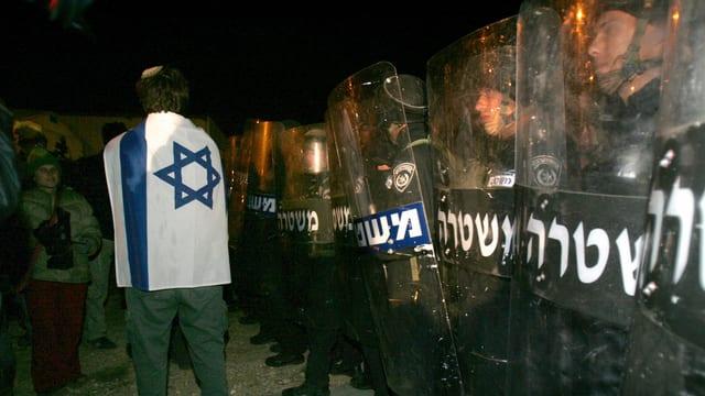 Ein Siedler im Westjordanland vor Polizeikräften.