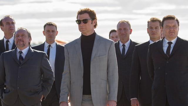 Filmstill: Ein Mann mit Sonnenbrille im hellen Anzug, umringt von dunkel gekleideten Herren.