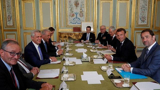 Mann an Tisch mit Leuten.