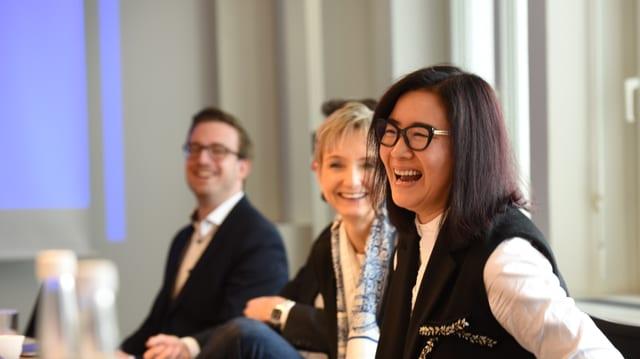 Eine chinesische Unternehmerin lacht an einer Pressekonferenz