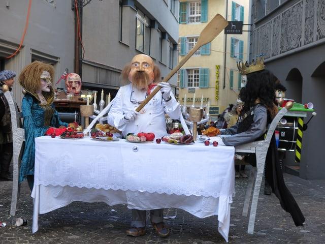 Fasnachtssujet mit einem gedeckten Tisch und zwei Personen am Essen.