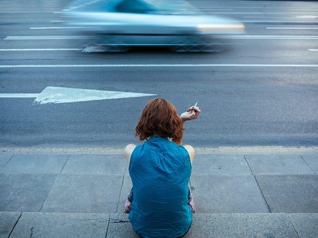 Eien Frau sitzen neben einer Strasse und hält eine Zigarette in der Hand.