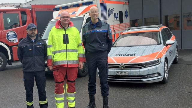 Die drei Einsatzleiter vor Polizei-, Rettungs-und Feuerwehrfahrzeugen