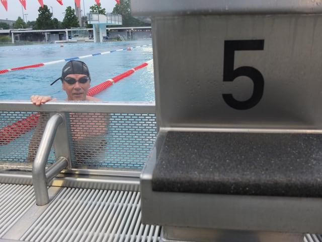 Mann mit schwarzer Badekappe und schwarzer Schwimmbrille im Wasser. Er hält sich am Geländer fest. Daneben ein kleiner Springturm mit der Nummer 5.