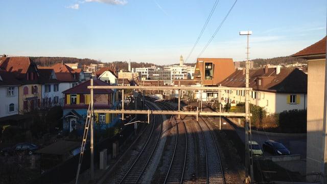 Bahngleise, verschiedene Häuser im Hintergrund.