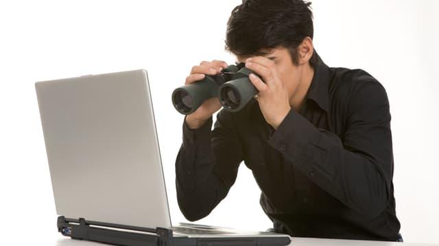 Ein Mann schaut mit einem Feldstecher in einen Computer.