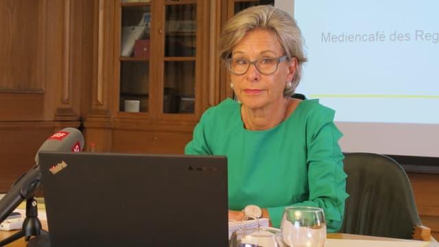 Frau sitzend hinter einem Laptop, vor ihr Mikrofon von Radio SRF