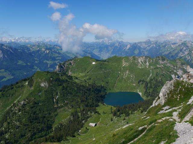 Vom Bergipfel erkennt man den Oberstocksee darunter, im Hintergrund weiter Berggipfel und zwei kleine Wolken, sonst ist der Himmel blau.