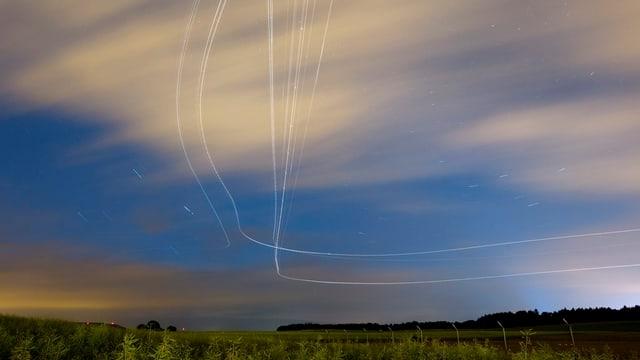Linien am Abendhimmel von Flugzeugen, die in Zürich gestartet sind.