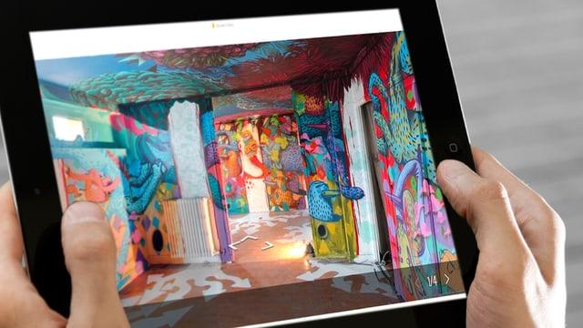 Man sieht den Tour 13 in Paris auf einem Tablet. Die Wände sind mit Graffitis bemalt.