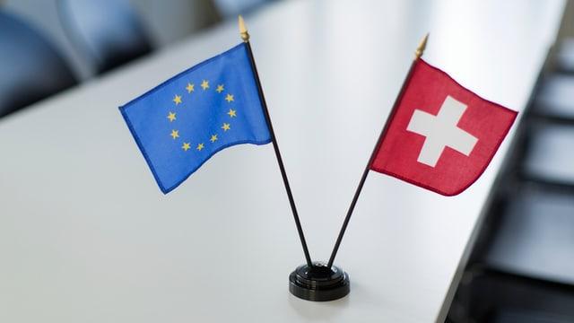 Die Flaggen der EU und der Schweiz stehen im Miniatur-Format auf einem Konferenztisch.