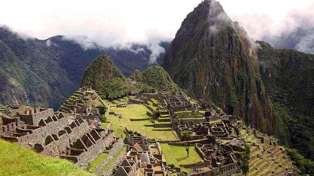 Die Ruinenstadt Machu Piccu in den Anden, eingebettet in einer grünen Berglandschaft.
