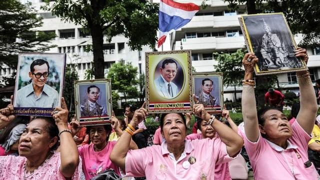 Thailänderinnen sitzen vor einem Gebäude und halten Fotos von Bhumibol in die Höhe.