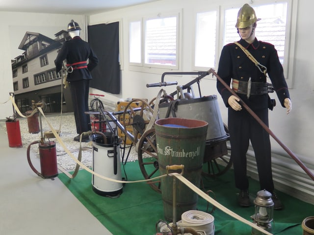 Löscheimer, Löschschläuche und zwei Puppen in alter Feuerwehruniform.