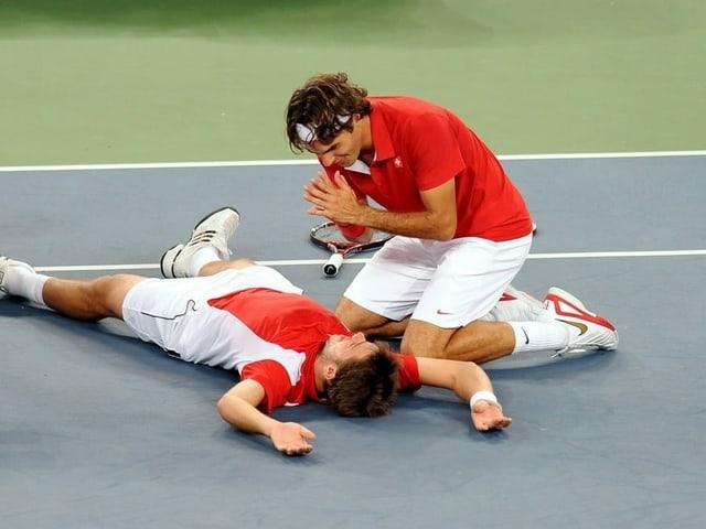 Roger Federer wärmt symbolisch seine Hände am brennenden Stan Wawrinka.