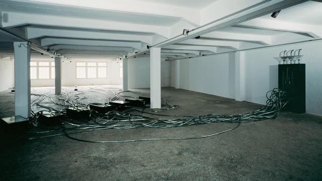 Ein raum, der aussieht wie eine Garage, es sind dunkle Kabel darin verteilt.