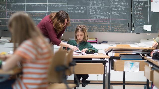 Lehrerin steht am Tisch eines sitznden Schülers und zeigt auf sein Buch. Im Vordergrund sieht man eine andere Schülerin, die ebenfalls an einer Schulbank sitzt.