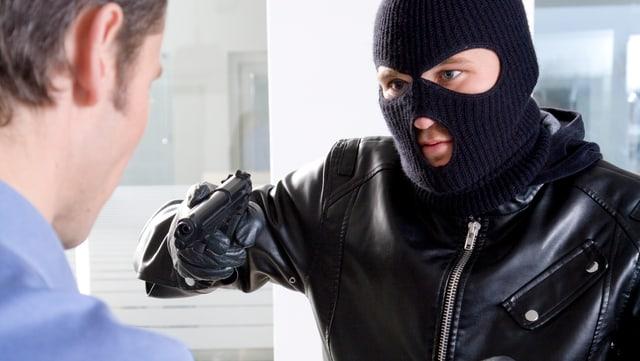 Ein masskierter Bankräuber bedroht mit einer Pistole einen Bankangestellten.