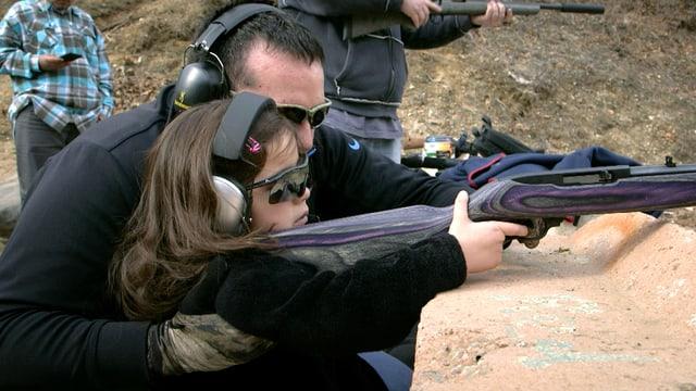 Ein Vater kniet neben seiner 5-jährigen Tochter, die mit dem Gewehr im Anschlag ein Ziel anvisiert.