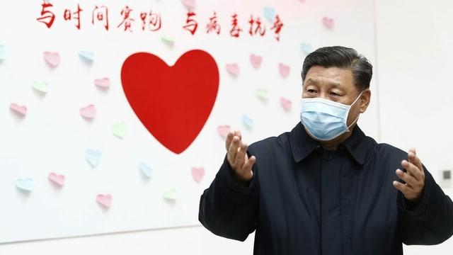 Xi Jinping mit Gesichtsmaske vor einem roten Herzen an der Wand.