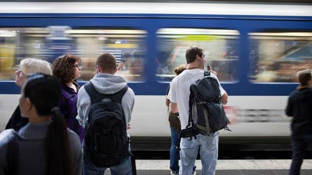 Jugendliche Pendler warten auf dem Perron, ein Zug fährt vorbei.