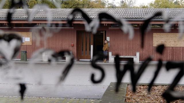 Durch eine mit Herzen verzierte Scheibe sieht man auf das Bundeszentrum in Bremgarten