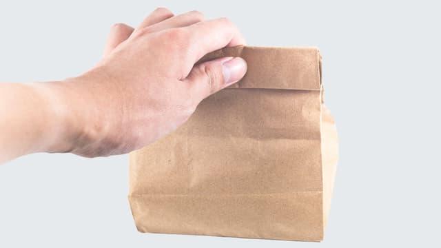 Ein Mann hält eine Papiertüte in der Hand