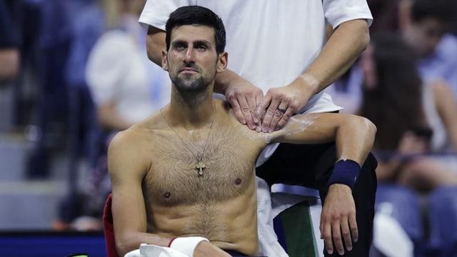 Purtret da Djokovic che sesa e lascha far massascha vi da sia spatla sanestra.