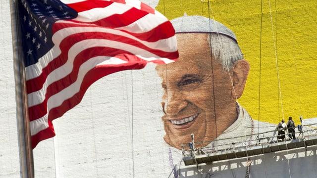Ein Bild der Papstes, das an die Wand gemalt ist. Neben dem Bild ist die amerikanische Flagge.