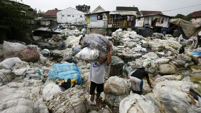 Philippinischer Mann der Plastik wegträgt.