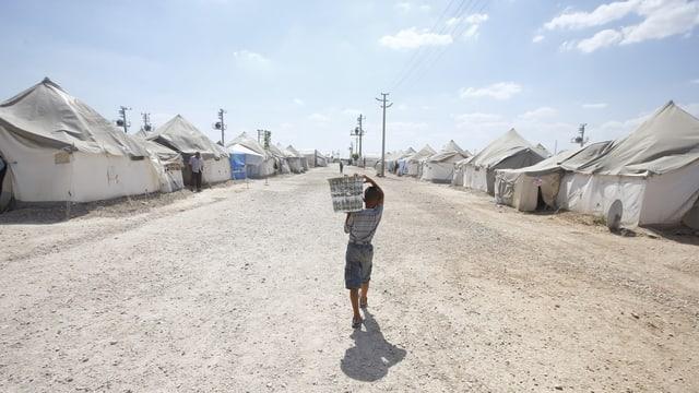Symbolbild: Flüchtlingslager mit Zelten, auf der breiten Mittelstrasse ein Junge mit einem Paket auf der Schulter.