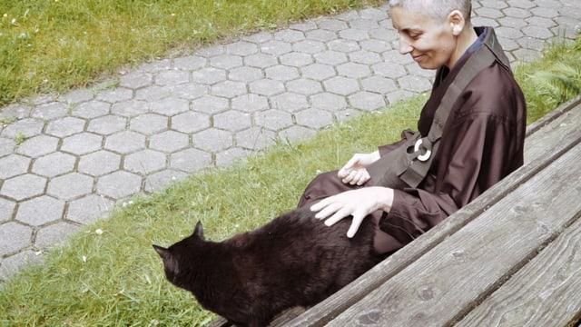 Eine Nonne streichelt eine Katze.