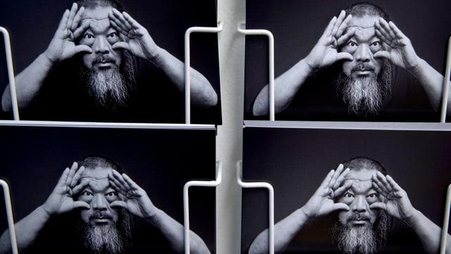 Vier gleiche Postkarten eines Mannes mit Bart nebeneinander. Darauf hält er jeweils mit Daumen und Zeigefinger die Augen auf.