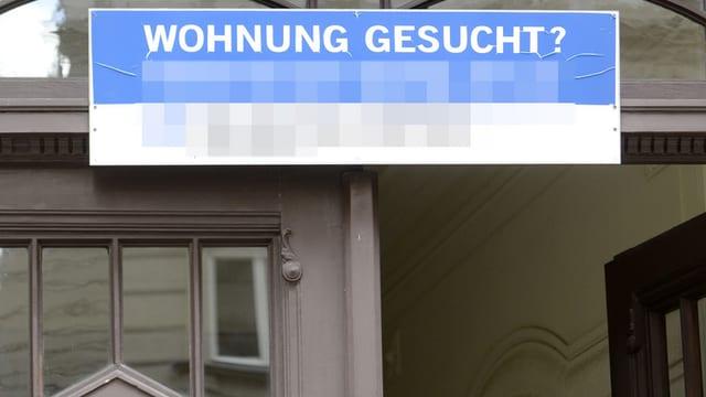 """Ein Schild an einem Haus mit der Aufschrift: """"Wohnung gesucht?"""""""