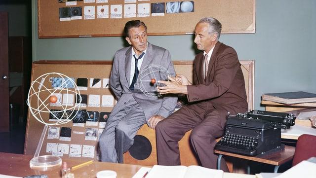 Zwei Männer: Einer hält ein Atom-Modell in der Hand.