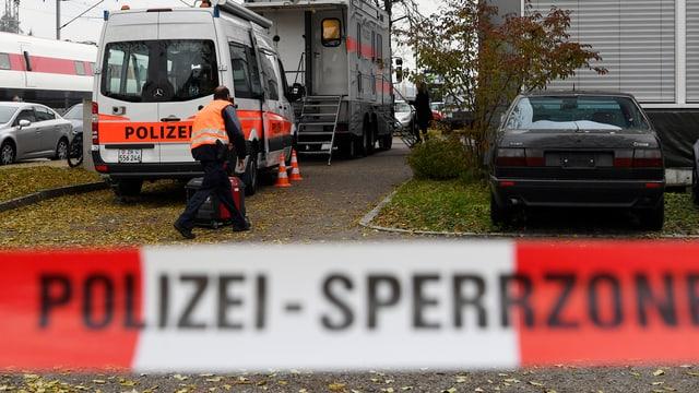 Polizeiauto und Polizisten vor Haus, vorne Absperrband