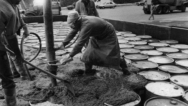 Arbeiter betonieren Fässer in der Sondermülldeponie Teuftal ein.