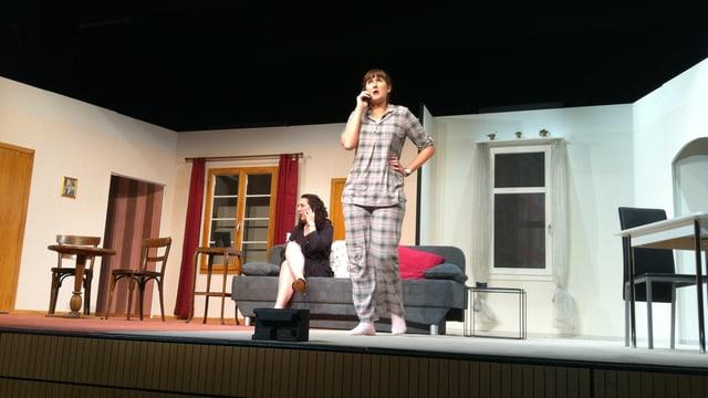Zwei Frauen auf einer Bühne, darauf steht ein Sofa.