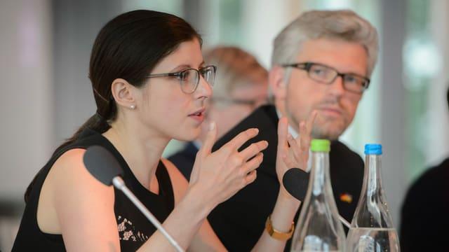 Frau mit Brille vor Mikrofon.