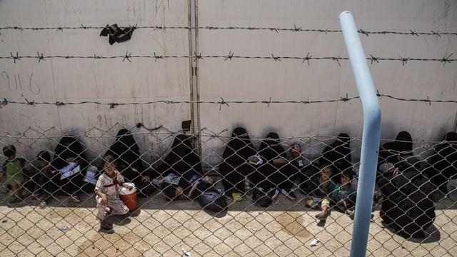 An einer Hauswand sitzen im Schatten Frauen und Kinder, davor ein Zaun mit Stacheldraht.