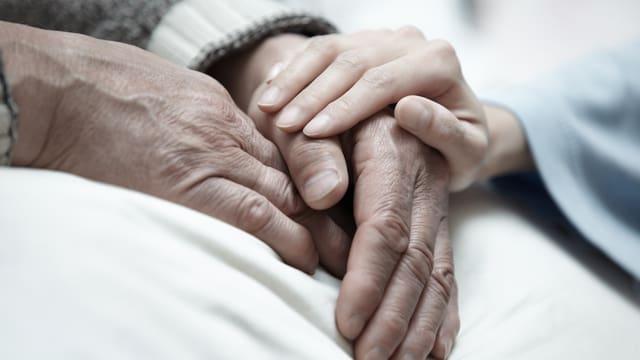 Frauenhand hält die Hände eines älteren Menschen
