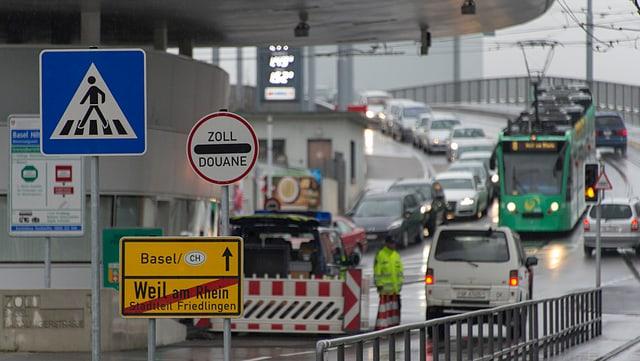 Das 8-ter Tram beim Grenzübergang Weil am Rhein, umgeben von vielen Autos.
