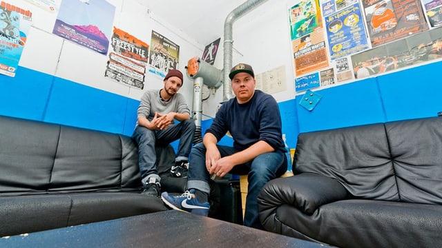 Zwei Rapper sind in der Mitte des Bildes zu sehen. Sie befinden sich auf der Sitzgruppe ihres Studios.