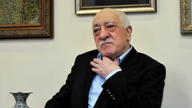 Prediger Gülen fasst sich an den Hemdskragen