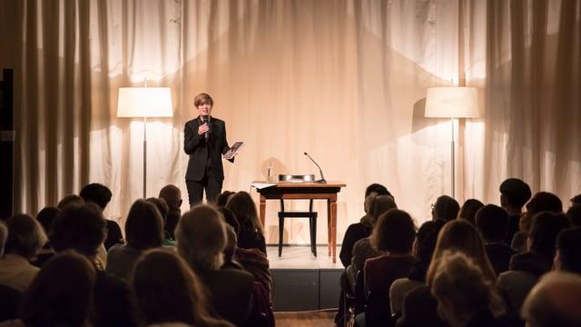 Eine Frau steht mit dem Mikrofon auf der Bühne, vor ihr ist ein Publikum zu sehen.