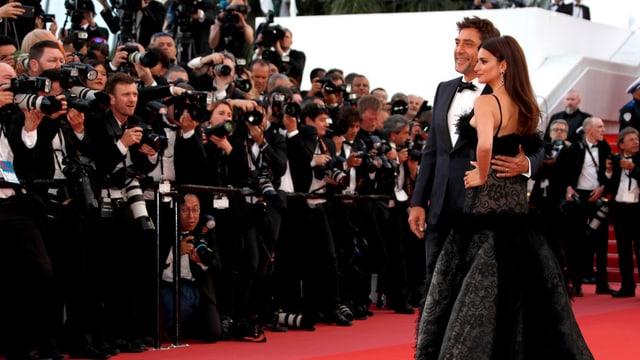 EIn Paar steht vor Fotografen.