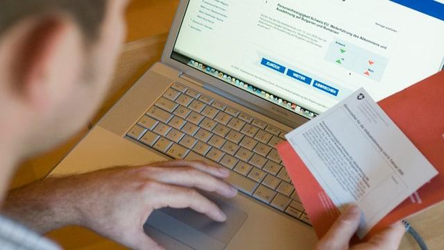 Ein Mann wählt elektronisch am Laptop