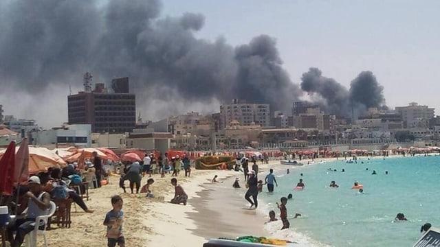 Hinter einem Strand mit Badenden steigt Rauch aus Gebäuden.