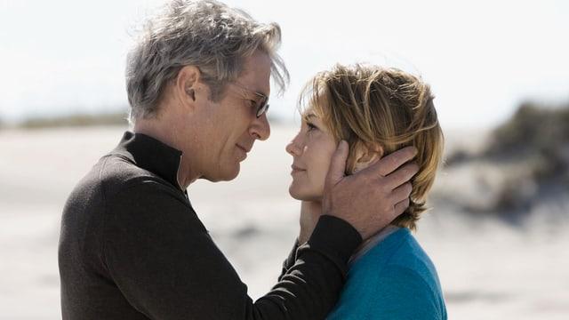 Mann Hält Kopf von Frau in den Händen; setzt an zum Küssen