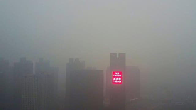 Eine chinesische Stadt im Smog. Die Hochhäuser schimmern durch den düsteren Smog, grell leuchtet eine digitale Schrifttafel mit chinesischen Zeichen.